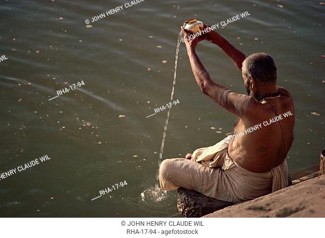 Hindu pilgrim pouring water libation to gods, wise ones or soul of departed, Varanasi, Uttar Pradesh state, India, Asia
