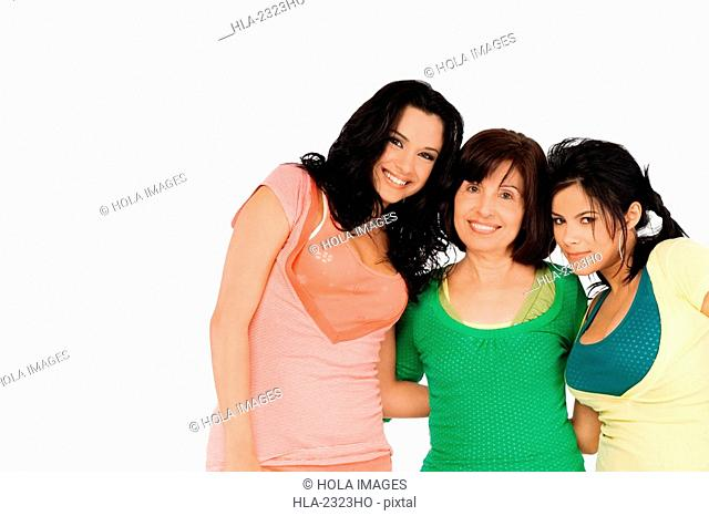 Portrait of a senior woman standing with her two daughters and smiling
