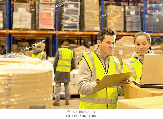 Workers using laptop in warehouse