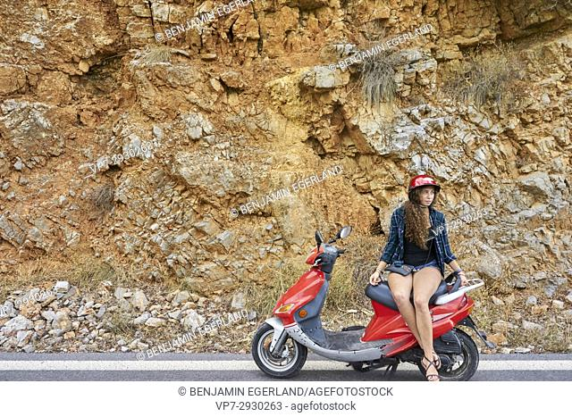 young girl sitting on moped against stone wall during travel adventure, near Heraklion, Crete, Greece