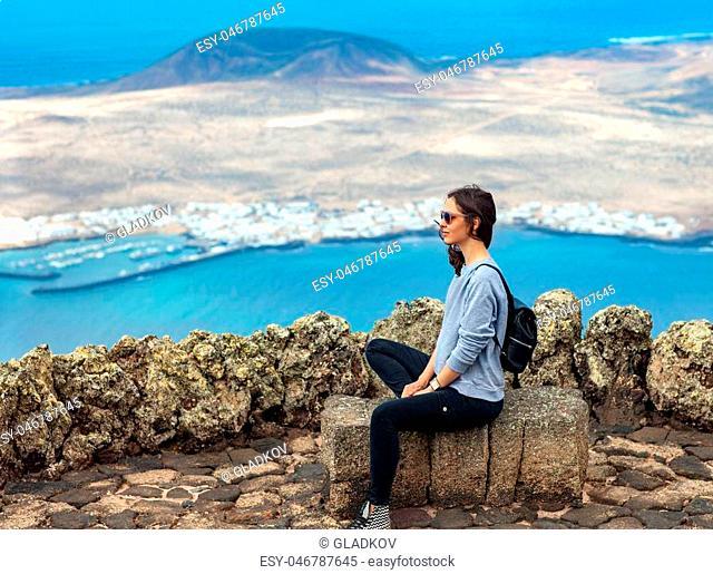 Traveler woman enjoying at viewpoint on island. Travel vacation concept. La Graciosa Island, Mirador del Rio, Lanzarote, Canary Islands, Spain