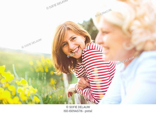 Portrait of two mature female friends leaning on fence, Tuscany, Italy