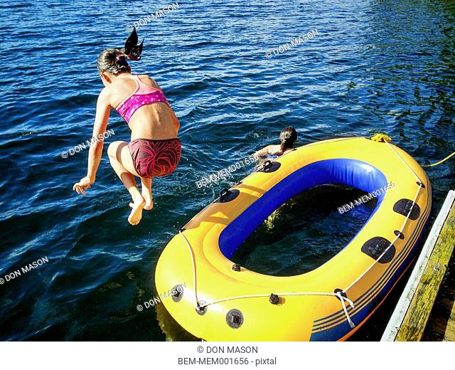 Mixed race girls playing on raft in still lake