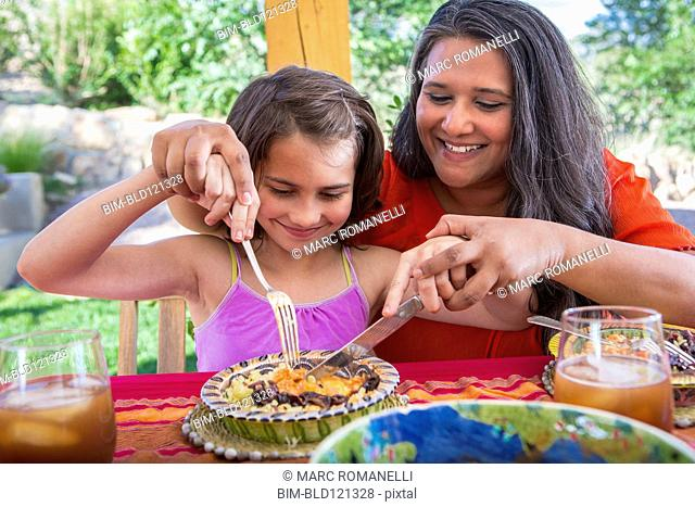 Mother and daughter eating at table