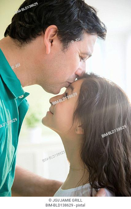 Hispanic father kissing daughter on forehead