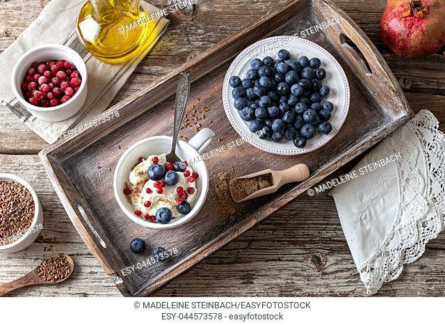 A cup of cottage cheese with ground linseeds, blueberries and frozen cranberries, with red currants and flax seed oil in the background