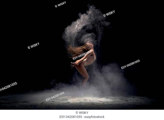 Contemporary art concept - young athletic dancer performing at dark studio in cloud of powder or dry paints