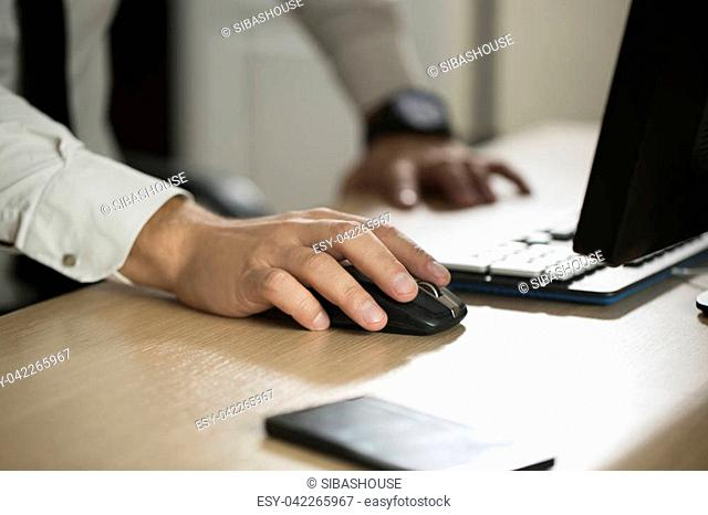 Hand of businessman use computer mouse and typing, partnership agreement form clipped to pad closeup. Business success, contract and important document