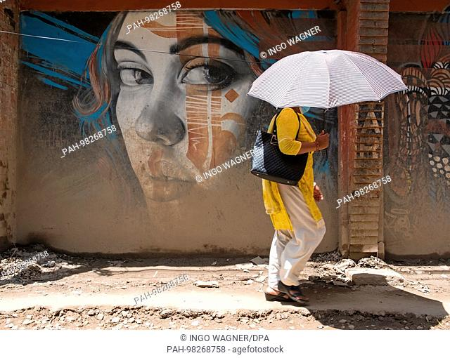 A woman walks past a wall painting on April 25, 2017 in the district of Thamel, Nepal's capital, Kathmandu. | usage worldwide. - Kathmandu/Nepal