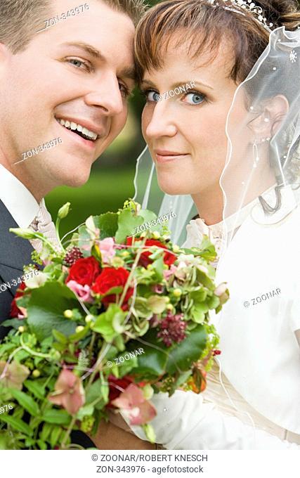 Portrait eines jungen Brautpaars mit Blumenstrauß