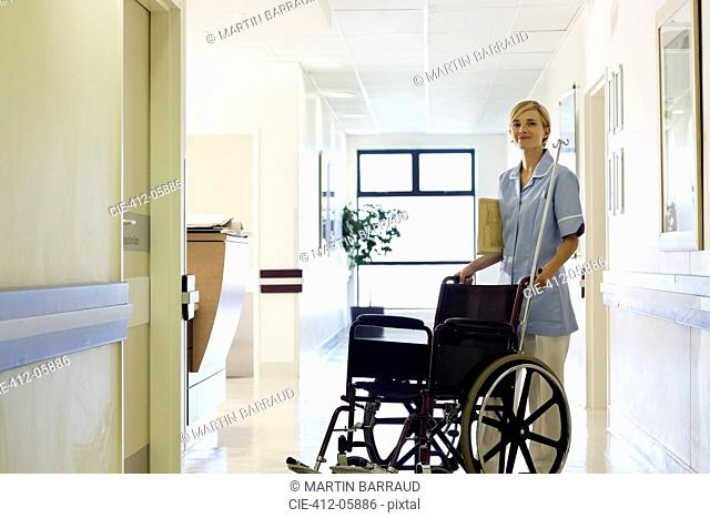 Nurse pushing wheelchair in hospital hallway