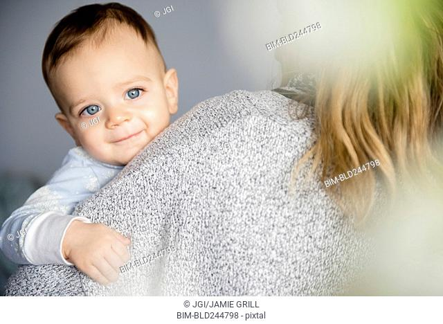 Caucasian baby boy smiling on shoulder of mother