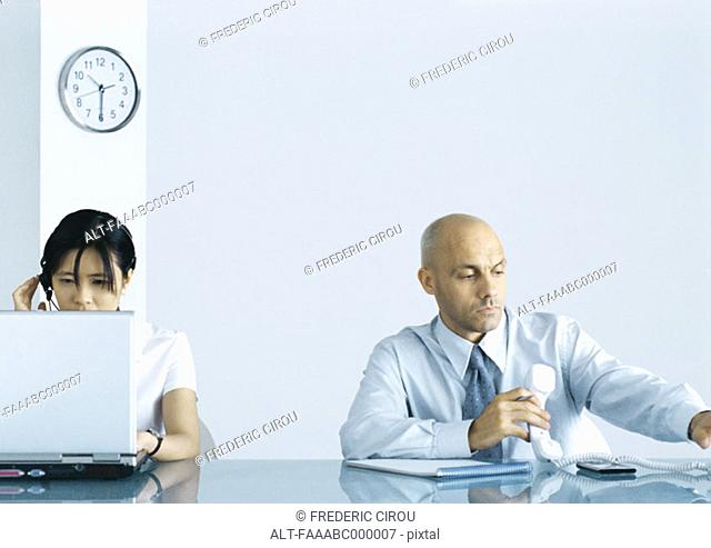 Office, man holding telephone while woman uses computer