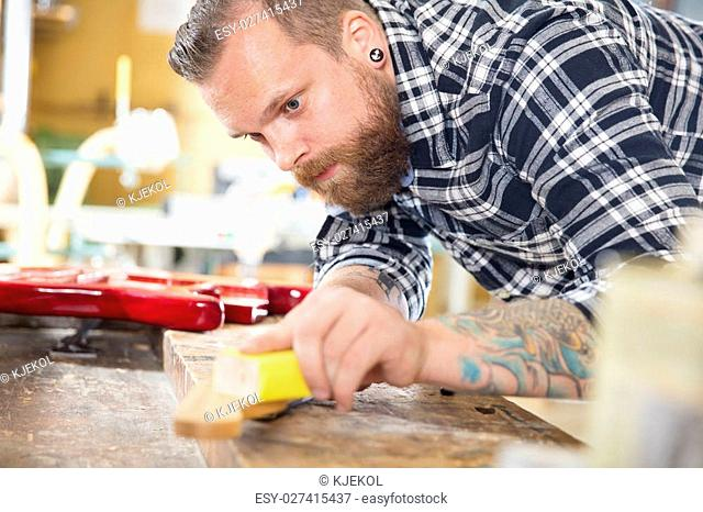 Craftsman using sanding paper on a guitar neck in a workshop for wood. Hard working man with tattoo and beard working with musical instruments