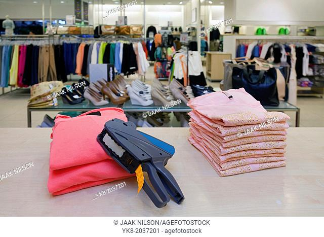 Pricing, store, desk.. Price gun on folded clothes of counter in retail shop interior