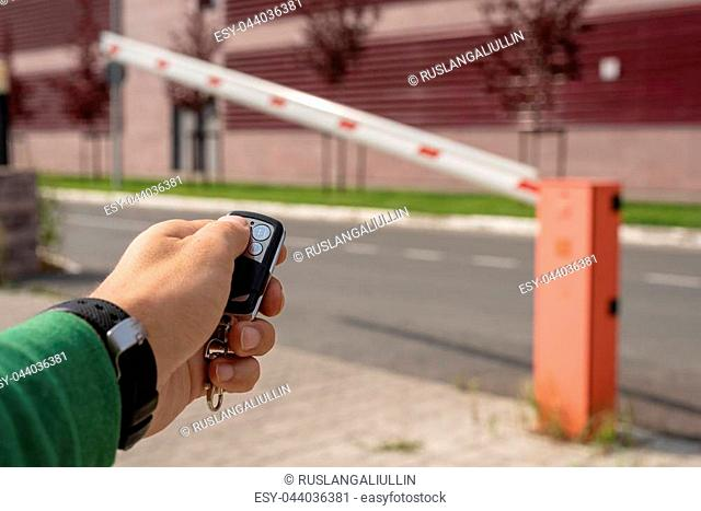 close up of a male hand with keychain from a barrier opens journey, remote control