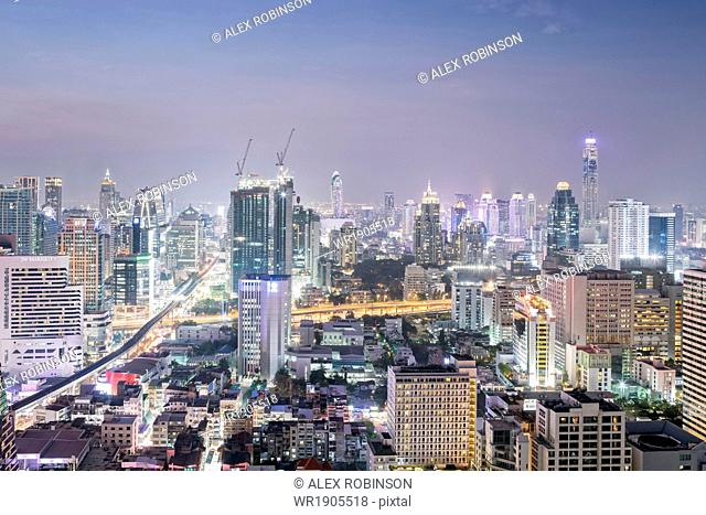 City skyline looking along the BTS Skytrain, Sukhumvit Road and Phloen Chit, with the Baiyoke Tower II to the right of frame, Bangkok, Thailand, Southeast Asia