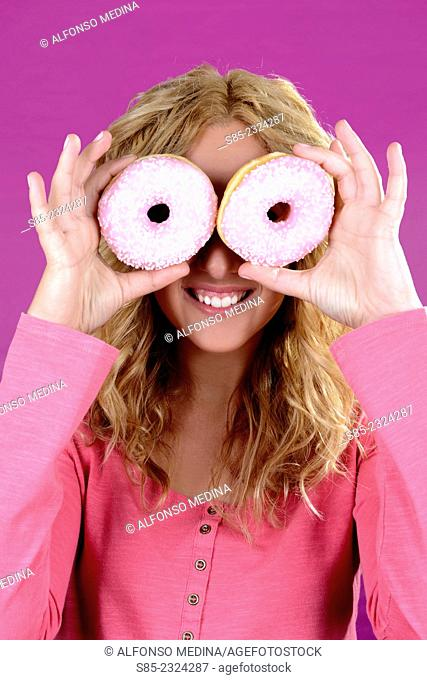Young blonde girl smiling and two donuts in the eyes