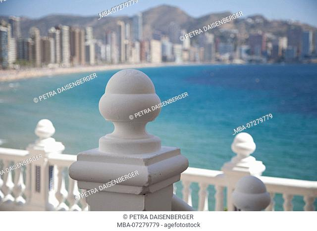 A stone palisade, in the background the skyline of Benidorm, Spain, Europe