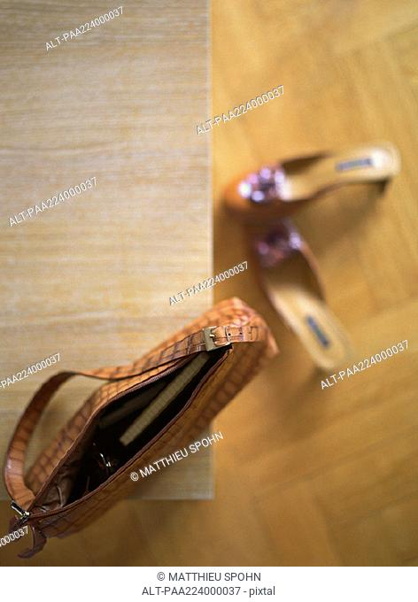 Purse on table, shoes on floor, high angle view