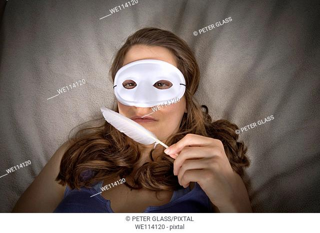Young woman in bed with a mask and feather