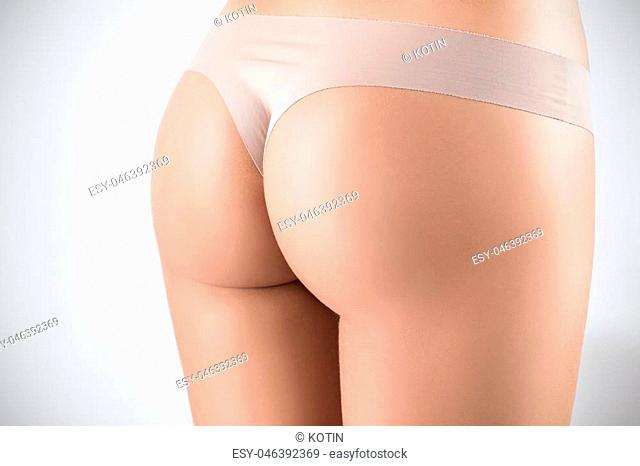 Beautiful perfect buttocks of young woman. Fitness concept. Over gray background
