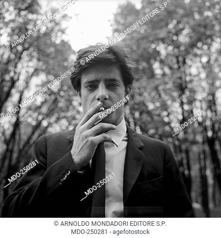 Giancarlo Giannini smokes a cigarette. Actor Giancarlo Giannini smokes a cigarette looking to camera in a confident way. Italy, 1966