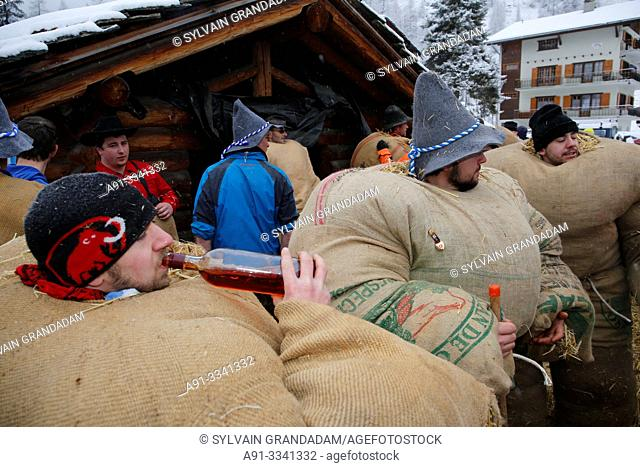 """Switzerland, Valais, Val d'Herens, village of Evolene, Carnaval, preparation of the """"empailles"""" ( young men dressed with old bags stuffed with about 50 kgs of..."""