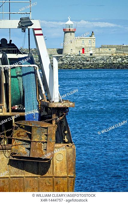 The Otter board and trawl nets of a trawler alongside the quay at Howth Harbour, with the East Wall lighthouse in the background, Howth, Co