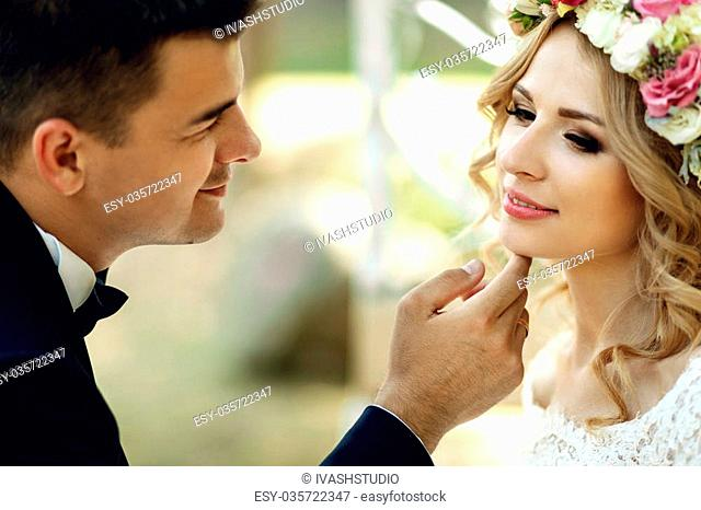 Handsome groom sensual touching emotional happy blonde bride in wreath in fairy-tale carriage close-up