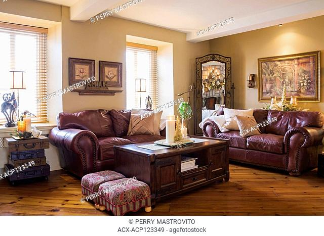 Burgundy leather sofas and wooden coffee table in living room inside an old renovated (circa 1840) Canadiana cottage style home, Quebec, Canada