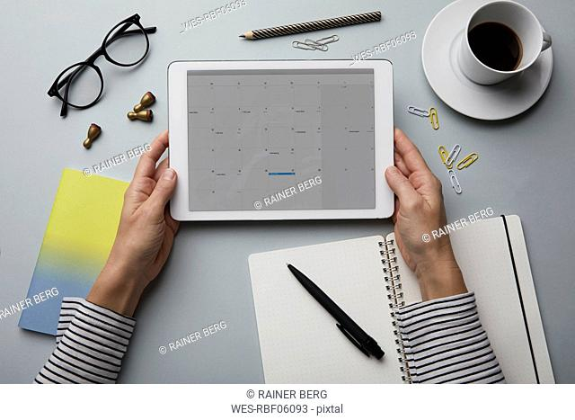 Top view of woman holding tablet with calendar on desk