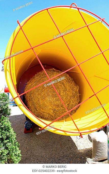 Straw bale roll in yellow rolling machine