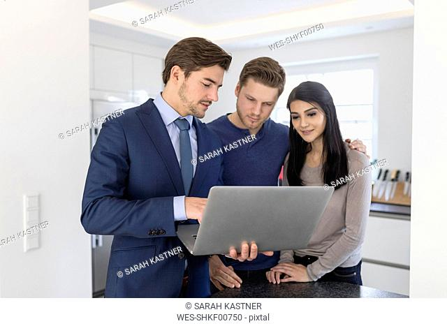 Consultant with laptop talking to couple at home