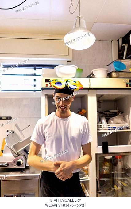 Portrait of funny pizza baker wearing clown's bow tie on his head