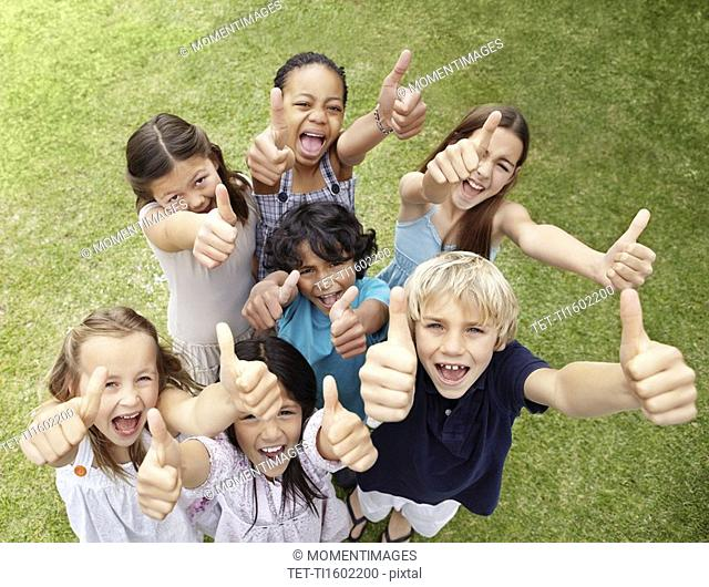 Group of children with their thumbs up