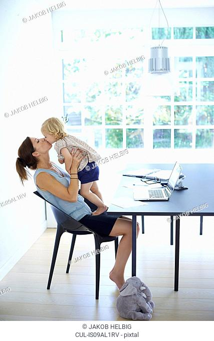 Mid adult woman holding up and kissing toddler daughter