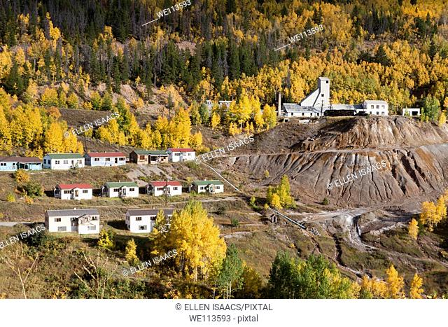 Mining town in Rocky Mountains of Colorado with simple houses on hillside with aspen trees in autumn