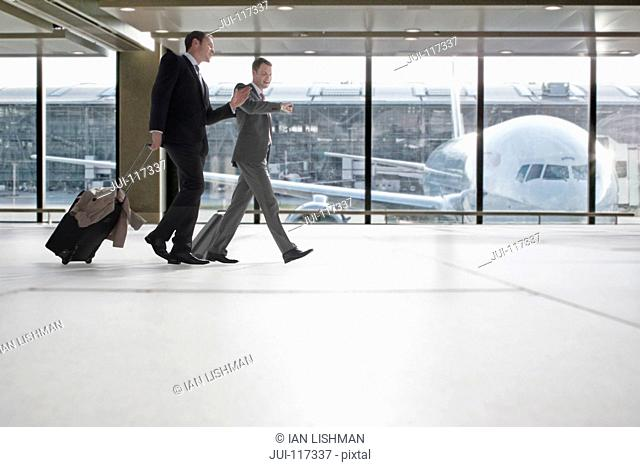 Businessmen With Luggage In Airport Departure Lounge