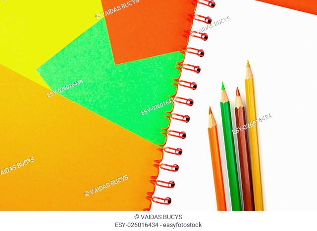 Color pencils, spiral notebook and colorful paper in background