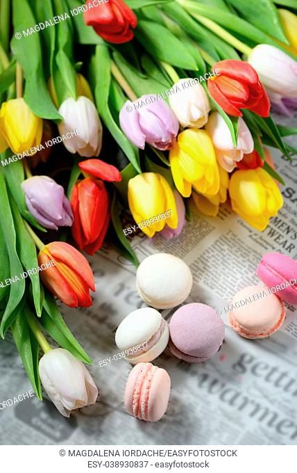 Colorful macaroons and tulips on newspaper
