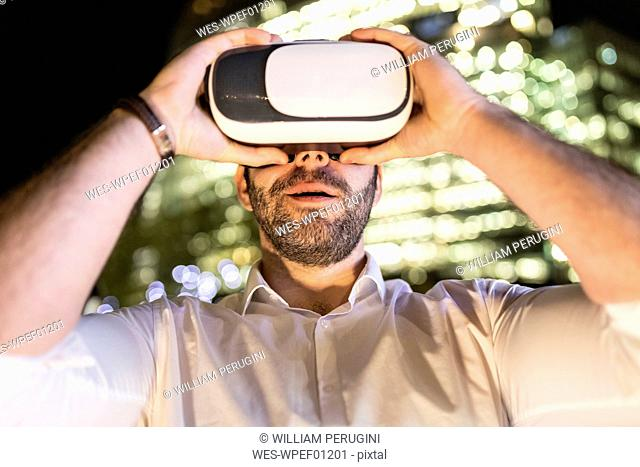 UK, London, man in the city wearing vr glasses by night