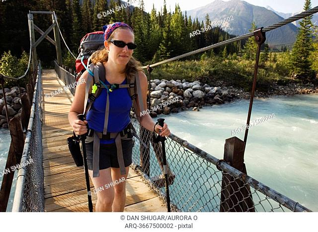 A female backpacker in her early thirties crosses a suspension bridge over the Vermillion River while hiking the Rockwall Trail, Kootenay National Park