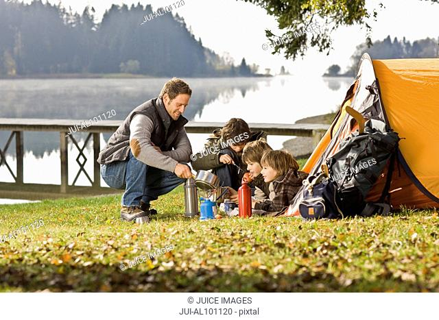 Father and sons camping and cooking near lake