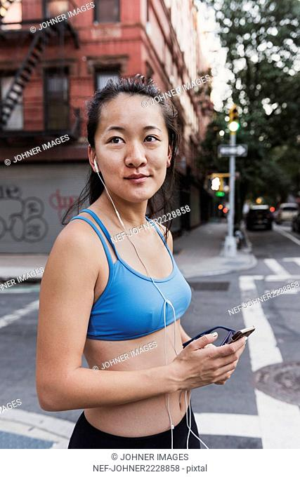 Smiling woman in sports bra listening music