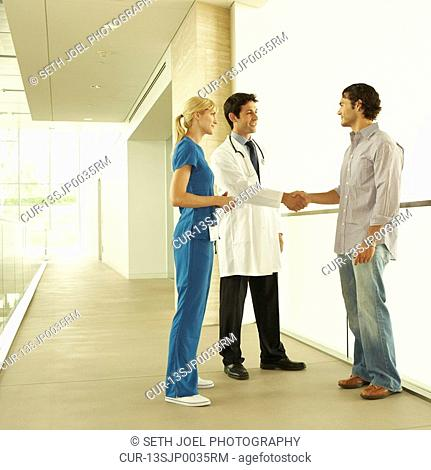 Doctor and nurse, wearing scrubs and lab coat, standing in hallway discussing care with patient or patient's family in modern hospital or clinic