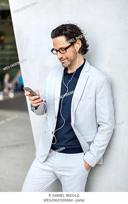 Businessman using smartphone with earphones