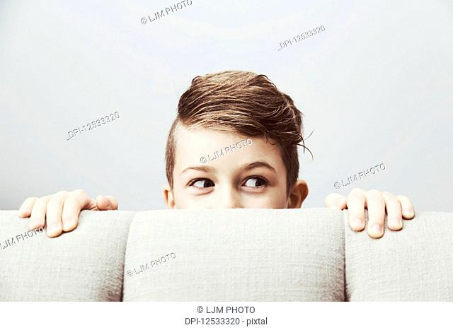 Portrait of a young boy peeking out from behind a couch with a silly facial expression; Langley, British Columbia, Canada