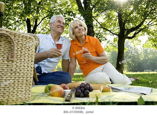 harmonious couple having picnic together in park, drinking from glasses