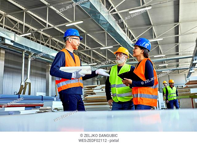 Colleagues in protective workwear talking in factory